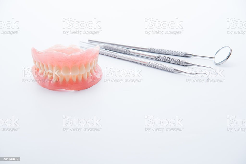Denture and dental tools,dental mirror on white background stock photo