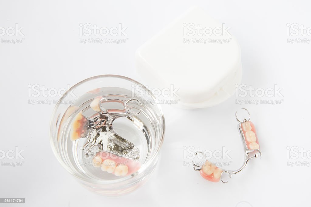 denture is cleaned in a glass of water. proper hygiene. stock photo