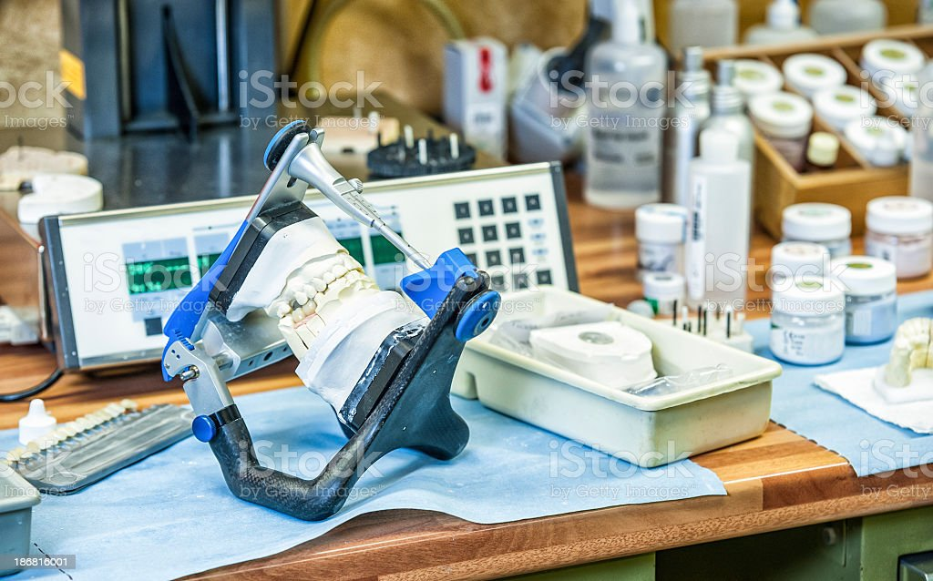 Dentures And Work Tools On A Desk royalty-free stock photo