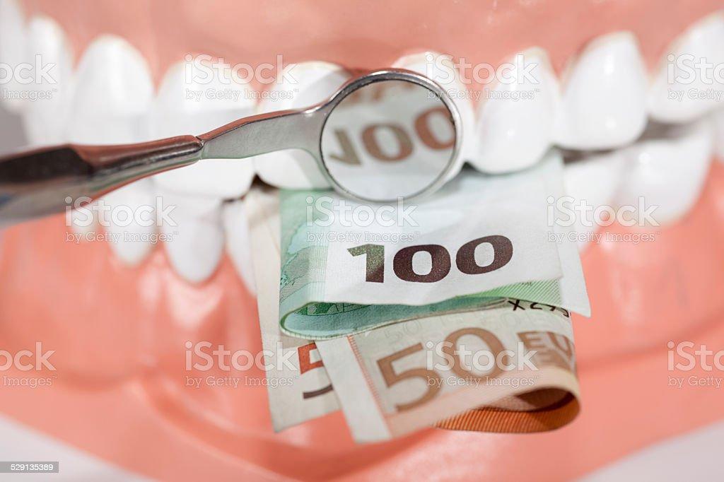 Dentures biting euro banknotes close up stock photo