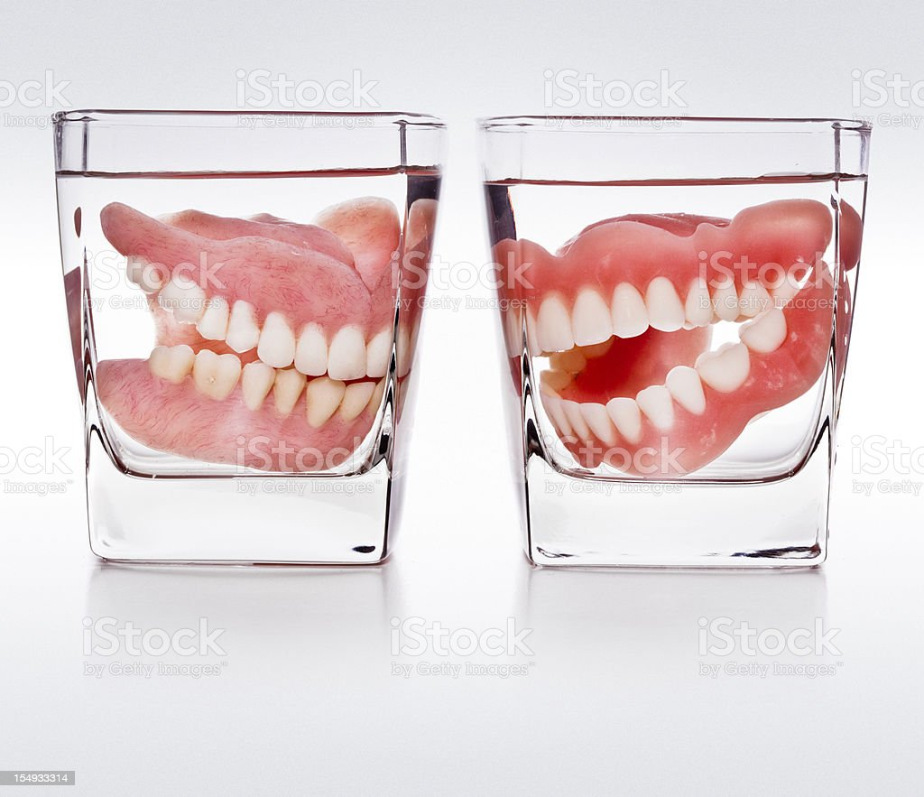 dentures in a glass of water stock photo