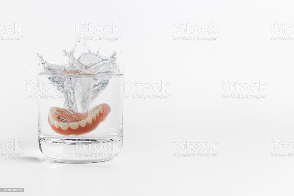 Dentures splashing in glass of water stock photo