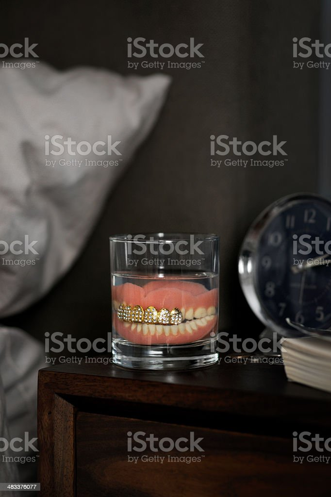 Dentures with grill in glass of water stock photo