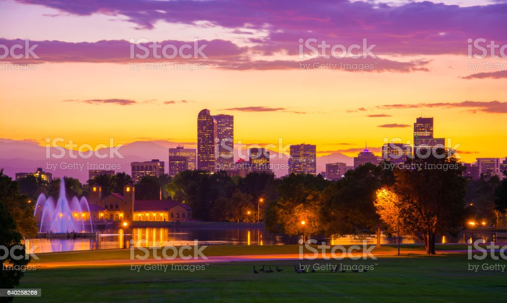 Denver skyline at sunset with fountains, lake, mountains, and geese stock photo