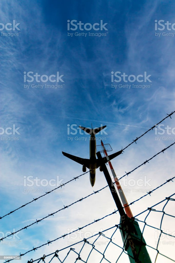 Departing Plane over Airport Fence stock photo