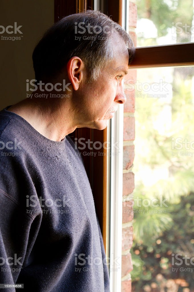 Depressed adult male stands and stares out the window. stock photo