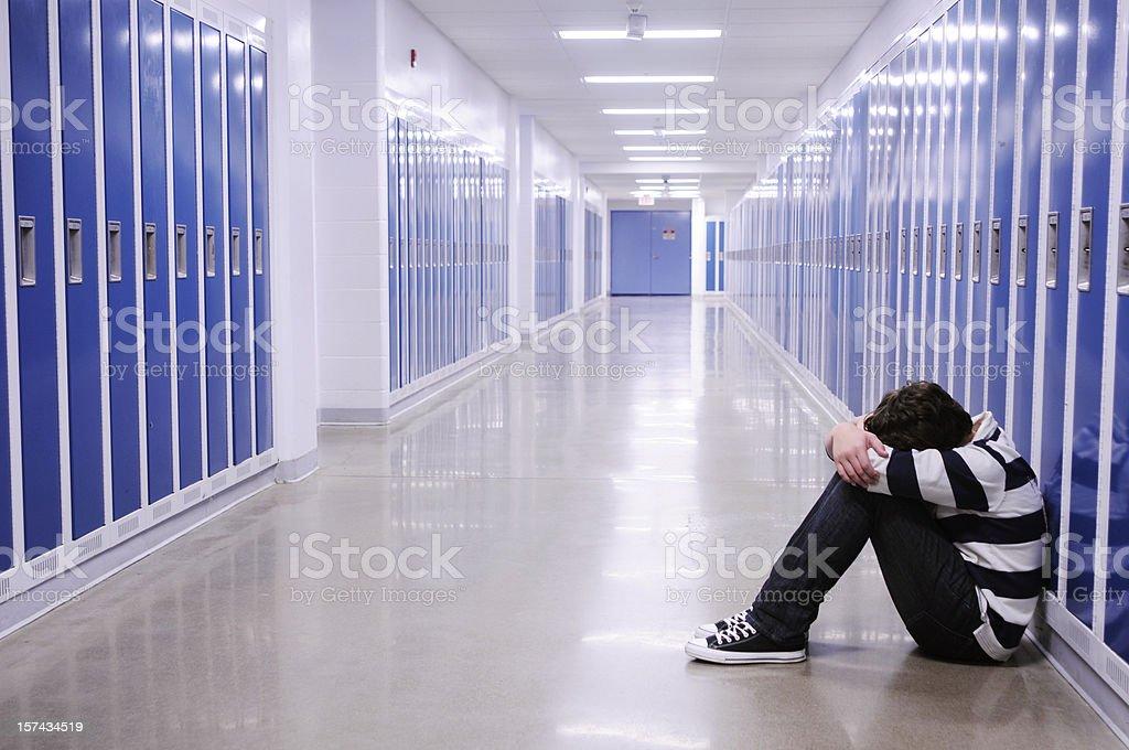 Depressed Boy in School Hallway stock photo