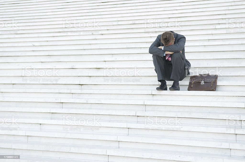 Depressed Businessman Hanging His Head Down on the Steps royalty-free stock photo