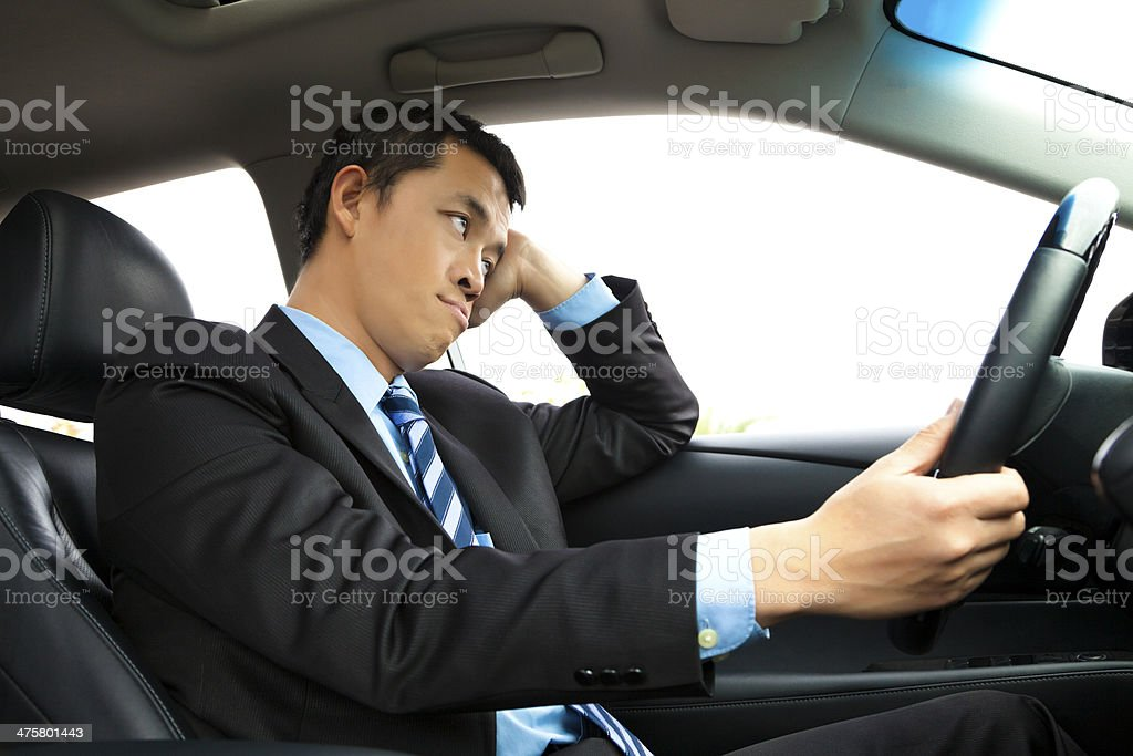 depressed businessman holding head and driving car stock photo