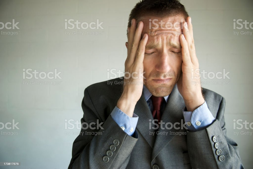 Depressed Businessman Holding Head in Hands with Expression of Grief royalty-free stock photo