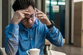 Depressed businessman in the coffee shop. Stressed businessman