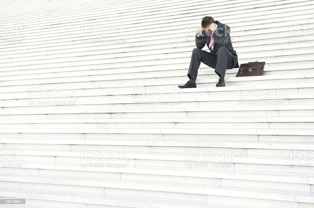 Depressed Businessman Sitting Outdoors on Steps with Head Down royalty-free stock photo