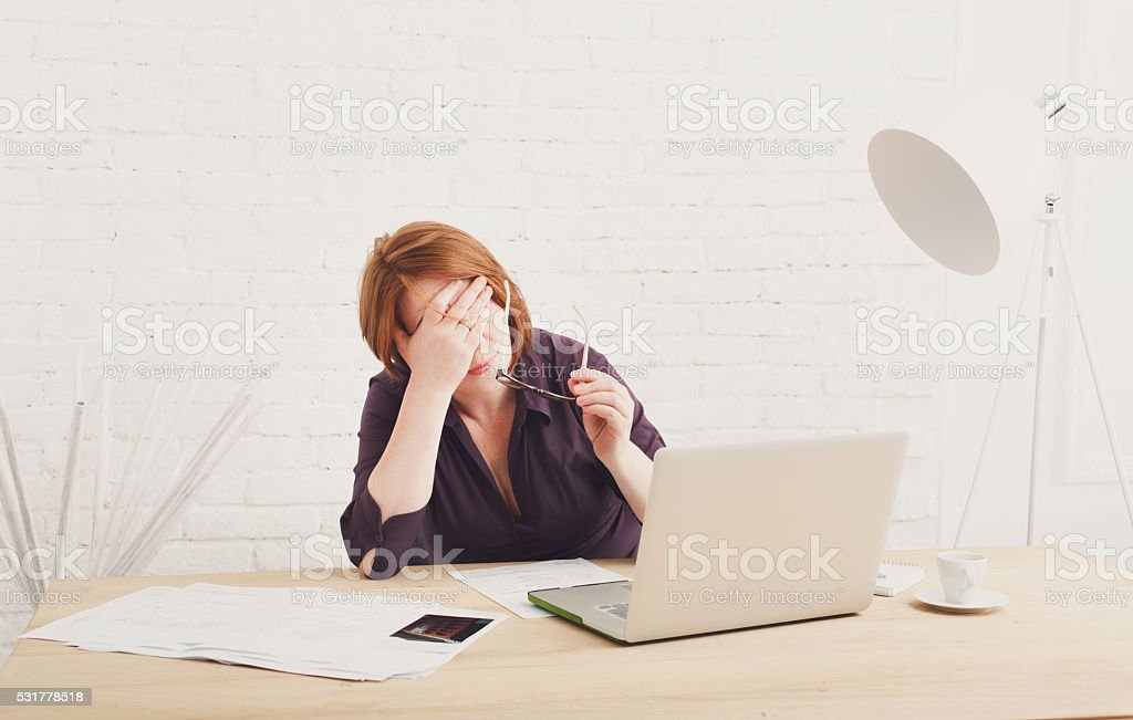 Depressed businesswoman in her office stock photo