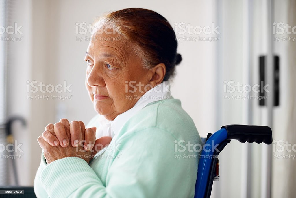 Depressed elderly woman with hands joined royalty-free stock photo