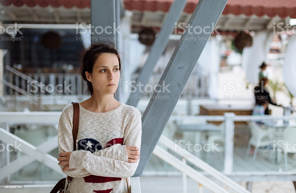 Depressed girl at the quay stock photo
