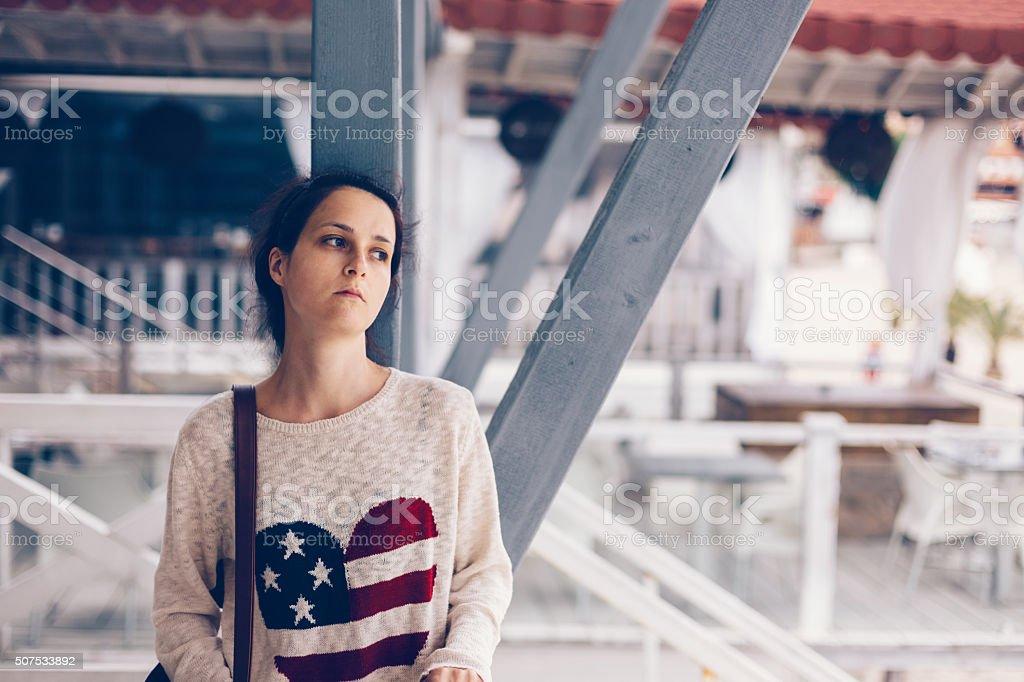 Depressed girl at the veranda staring away stock photo