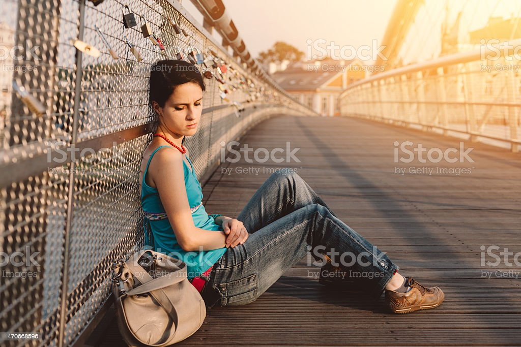 Depressed girl sitting at the ground stock photo