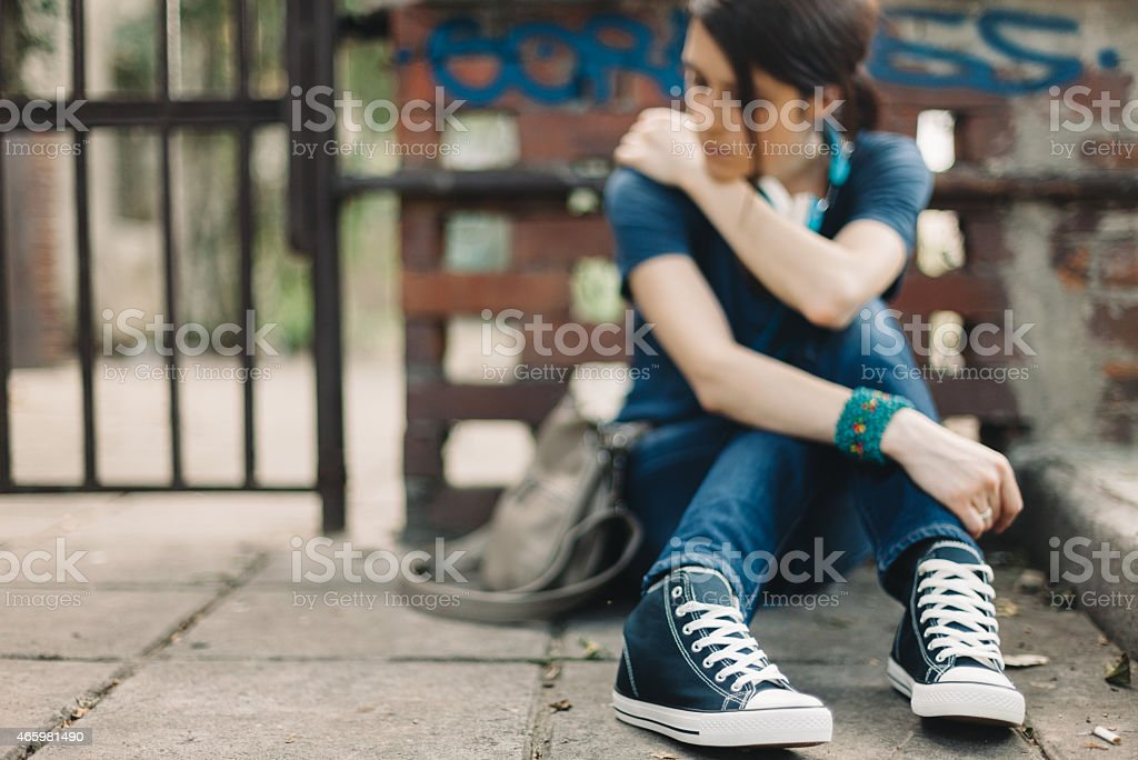 Depressed girl sitting on the ground stock photo