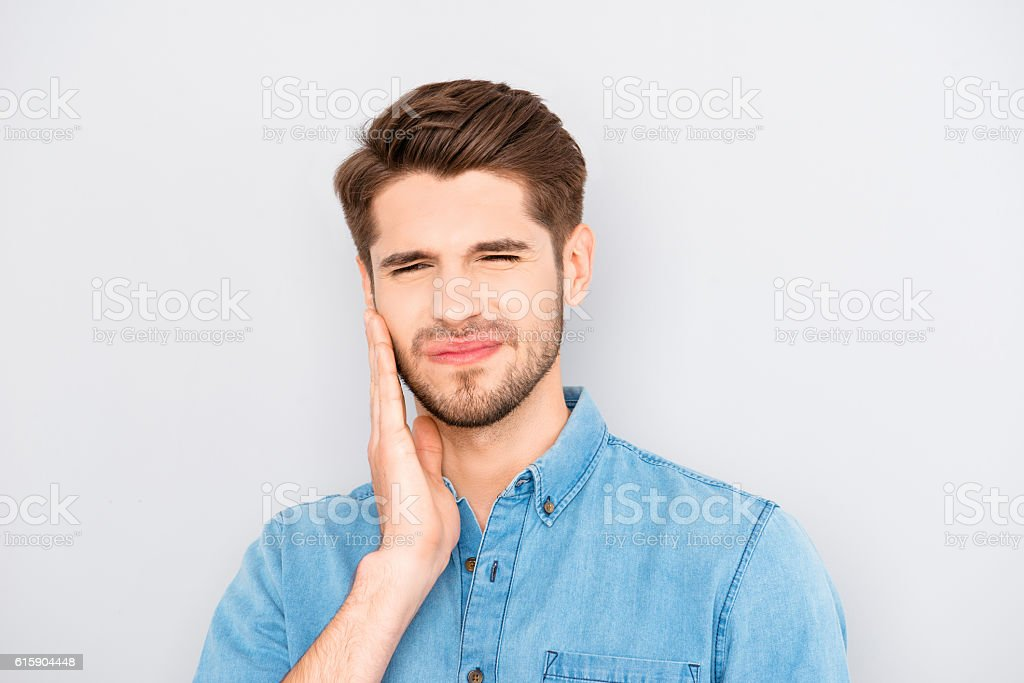 Depressed ill man having toothache and touching cheek stock photo