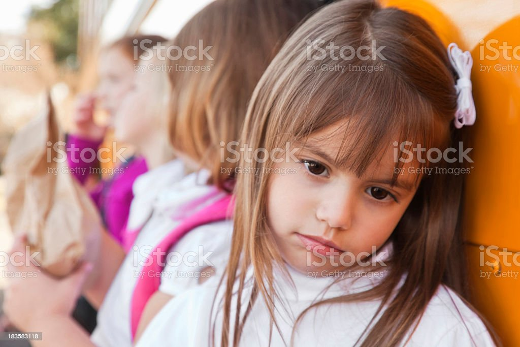 Depressed Little Girl Leaning on School Bus With Other Students stock photo