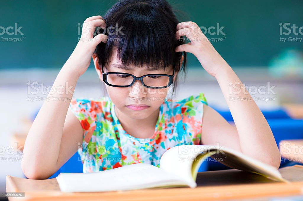 Depressed little girl studing in the classroom stock photo