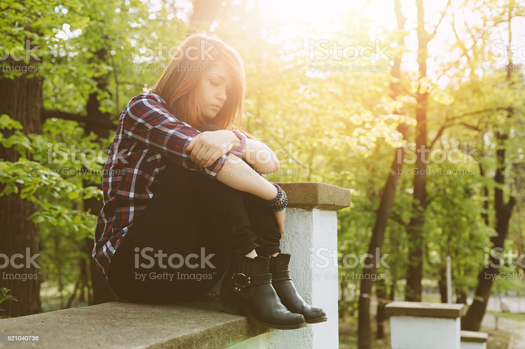 Depressed lonely teenager in the park stock photo