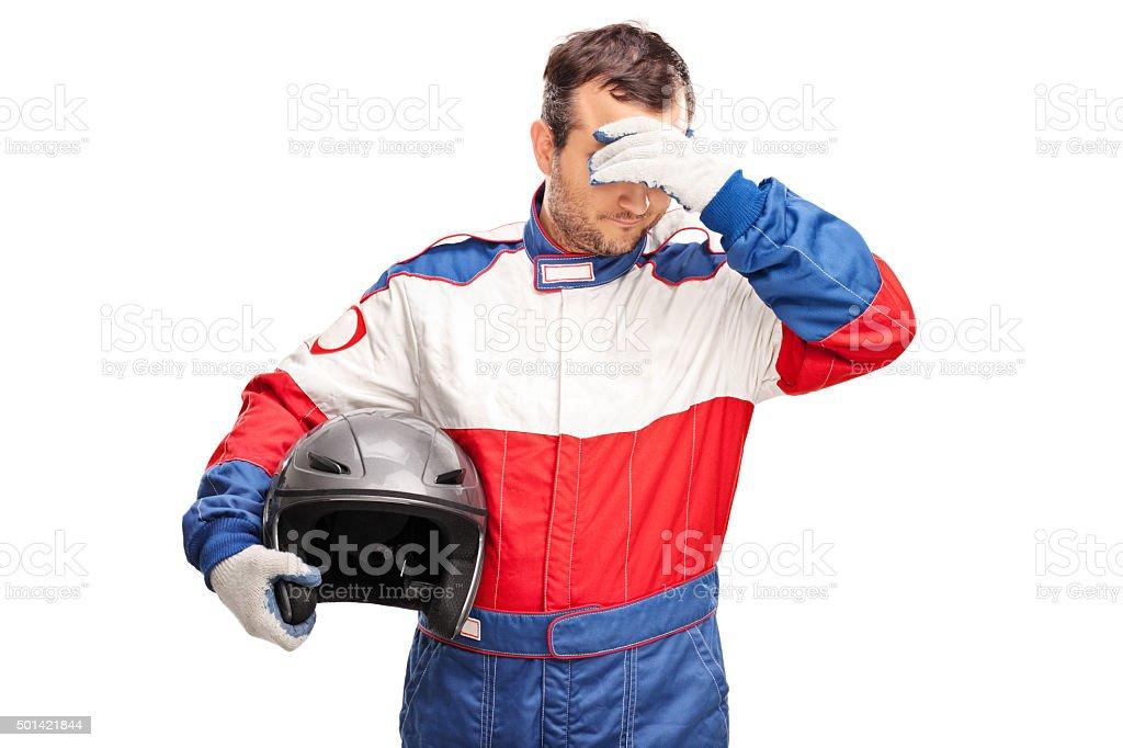 Depressed male car racer holding a helmet stock photo