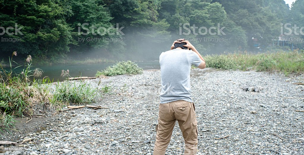 Depressed man by the river stock photo