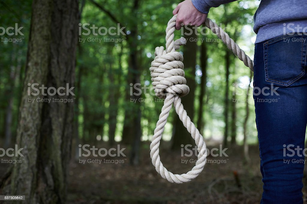 Depressed Man Contemplating Suicide By Hanging In Forest stock photo