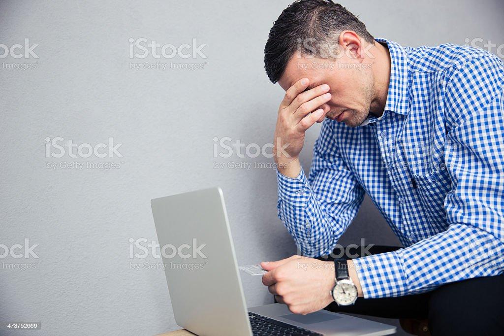 Depressed man holding credit card stock photo