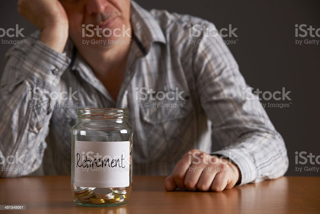 Depressed Man Looking At Empty Jar Labelled Retirement royalty-free stock photo