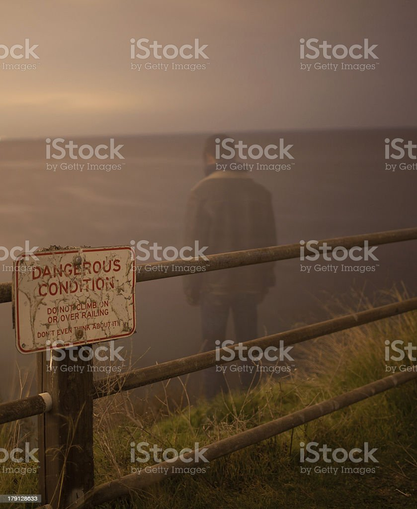 Depressed man looking over edge of cliff royalty-free stock photo