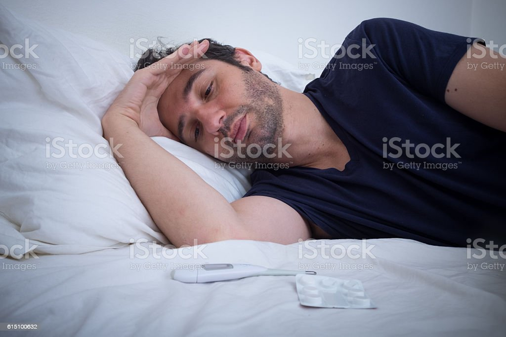 Depressed man lying in his bed and feeling bad stock photo
