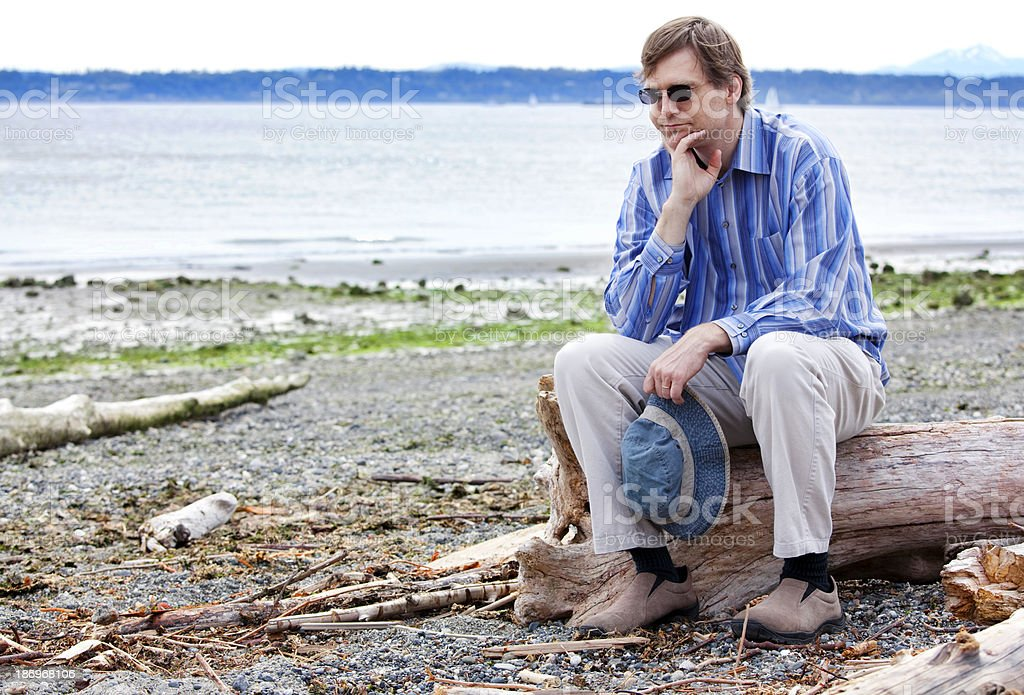 Depressed man sitting on driftwood along beach royalty-free stock photo