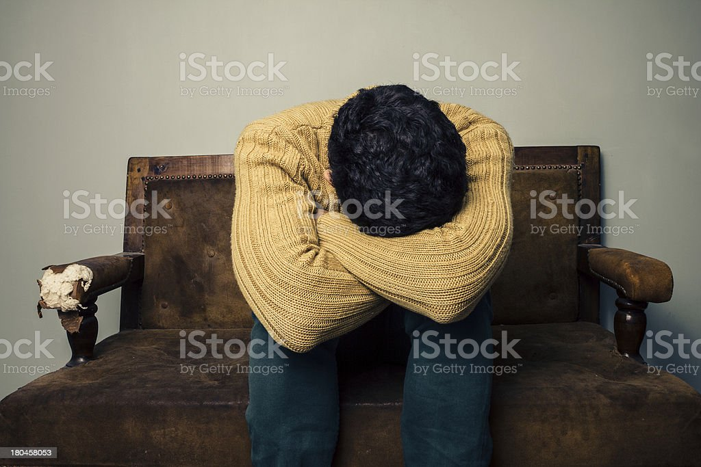 Depressed man sitting on old sofa stock photo