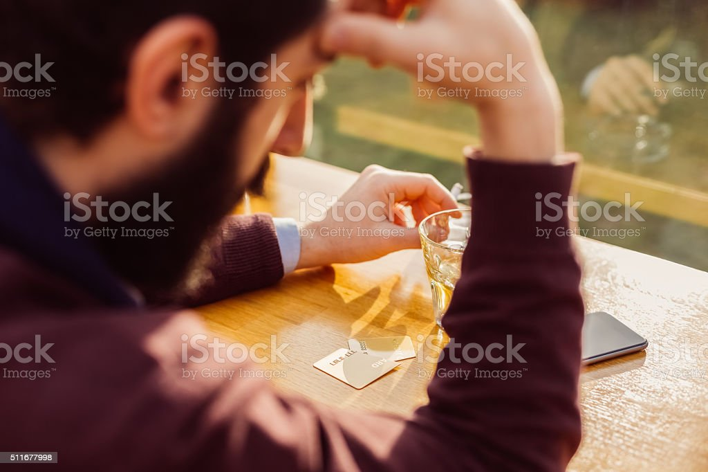 Depressed man with credit card cut in half stock photo
