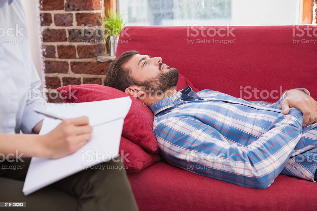 Depressed patient lying on couch stock photo