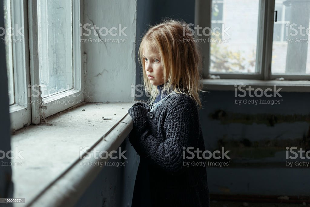 Depressed poot girl standing near window stock photo