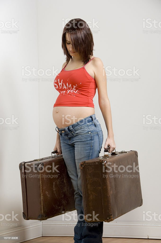 depressed pregnant woman carrying suitcases stock photo