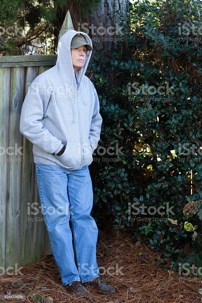 Depressed senior adult male outside leans against a tree. stock photo