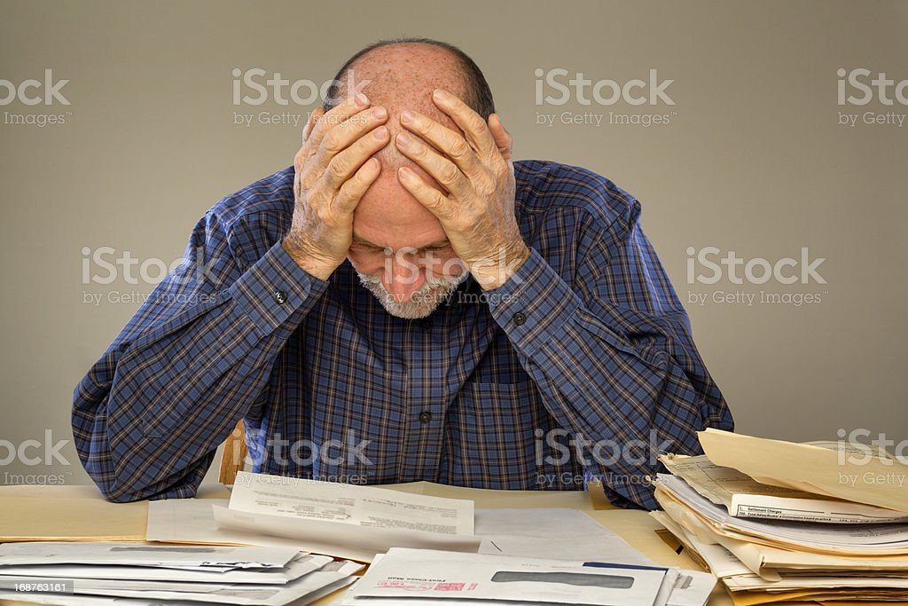 Depressed Senior Adult Man With Stacks of Papers and Envelopes stock photo