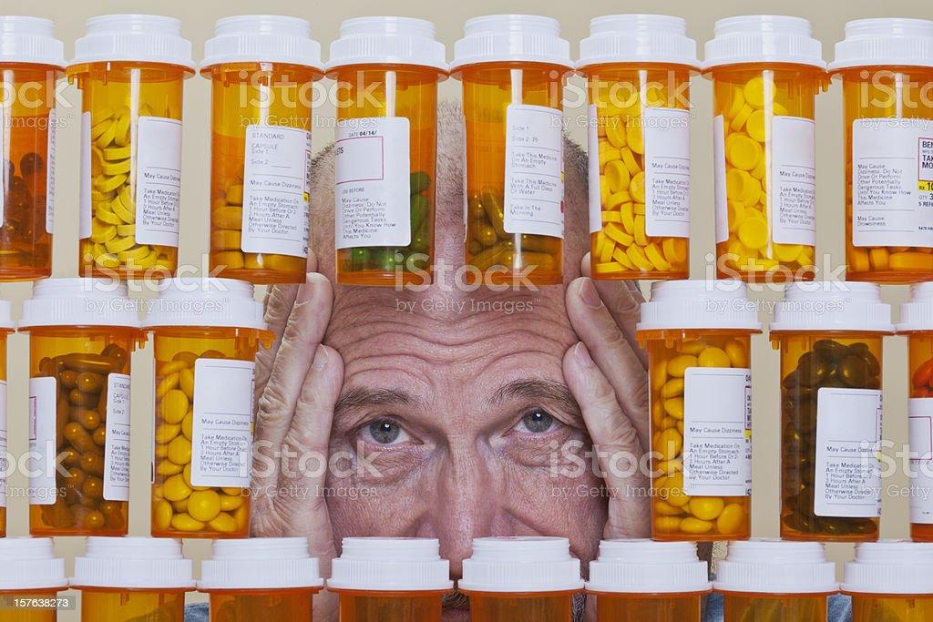 Depressed Senior Man Looking Through Rows of Prescription Medication royalty-free stock photo