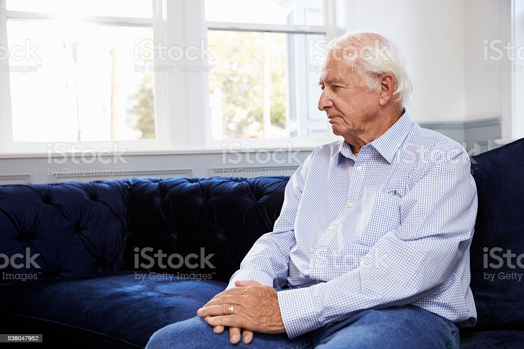 Depressed Senior Man Sitting On Sofa At Home stock photo