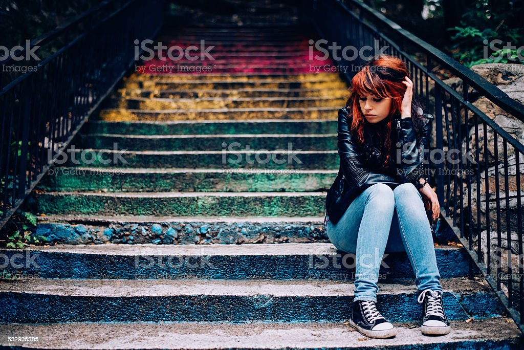 Depressed teenager sitting lonely outdoors stock photo
