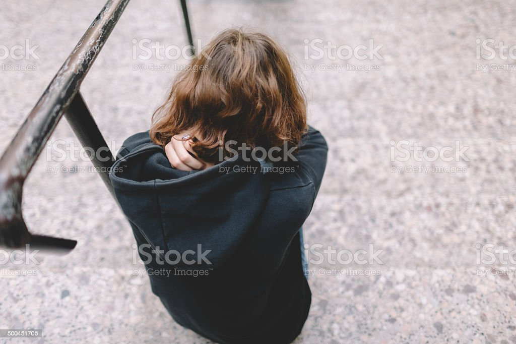 Depressed teenager sitting on the stairs stock photo