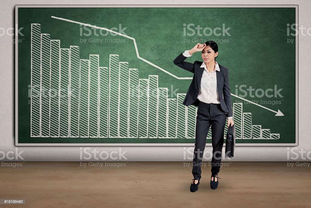 Depressed woman and declining graph stock photo