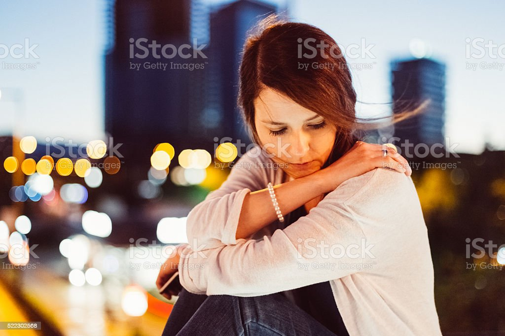 Depressed woman at the bridge stock photo