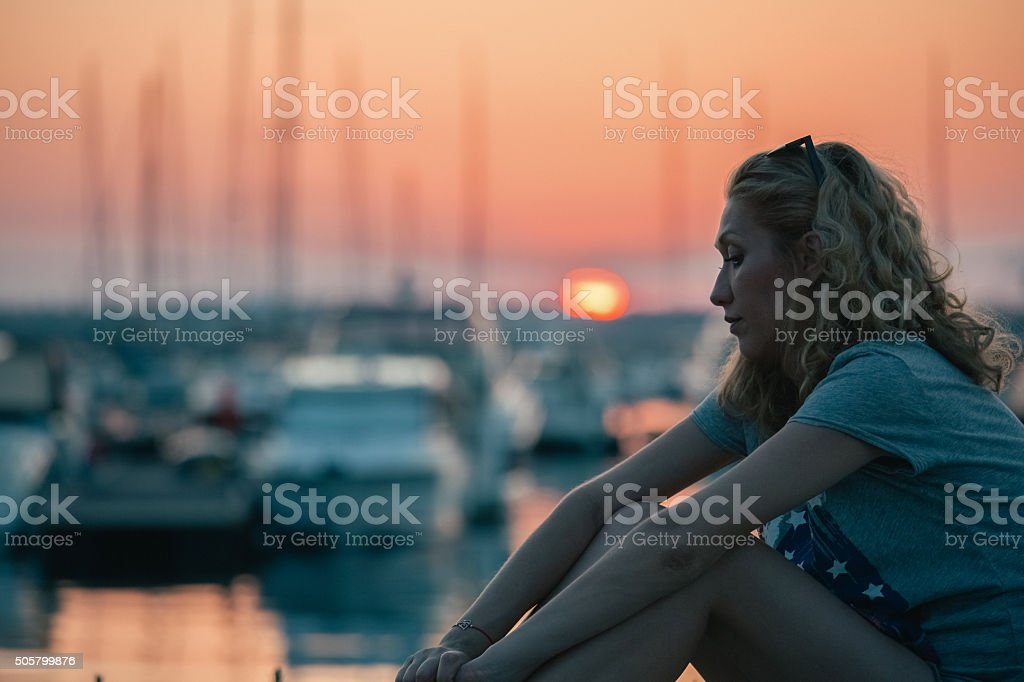 Depressed woman at the yacht port stock photo