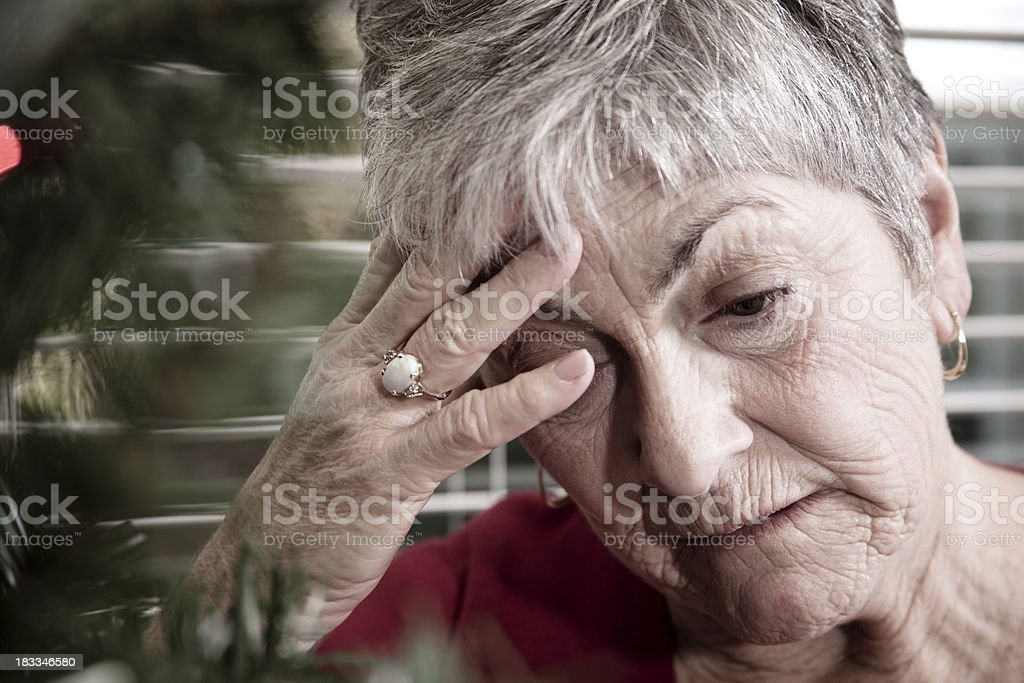 Depressed woman by Christmas tree. royalty-free stock photo