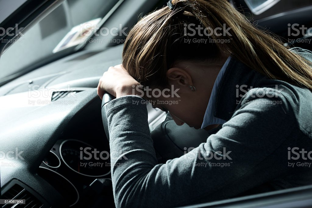 Depressed woman in a car stock photo